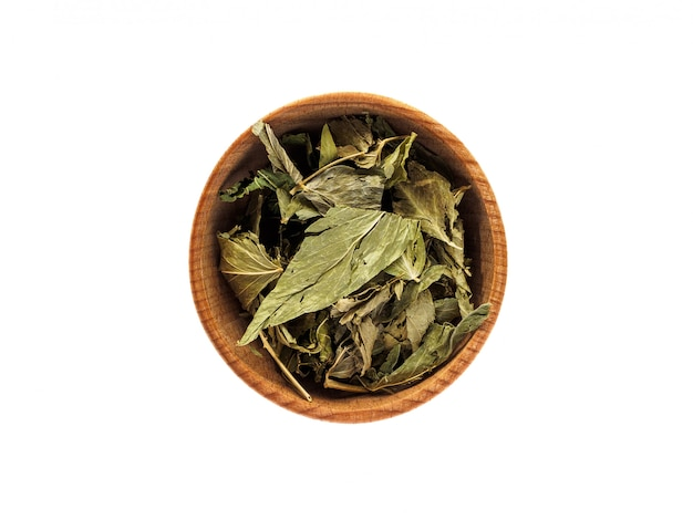 Dry leaves of galega officinalis in a wooden cup on a white table