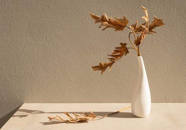 アースカラーのテーブルに美しい白いセラミック花瓶の乾燥した葉フィロデンドロンザナドゥ植物熱帯観葉植物
