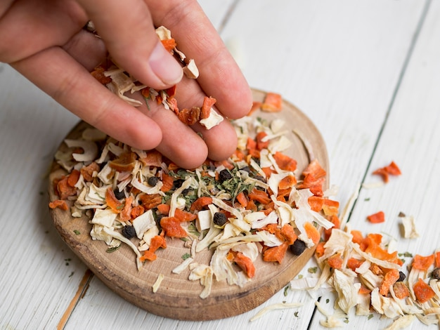Dry leaves and spices on round wooden tray