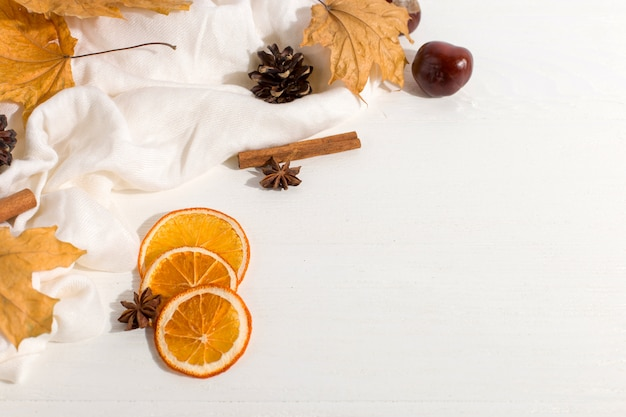 Dry leaves, spices, scarf and oranges on the table. autumn mood, copyspace, morning light.