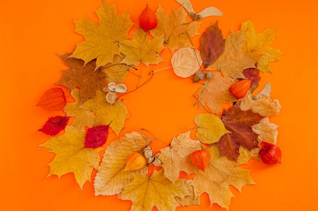 オレンジ色の背景に乾燥した葉の花輪フレーム