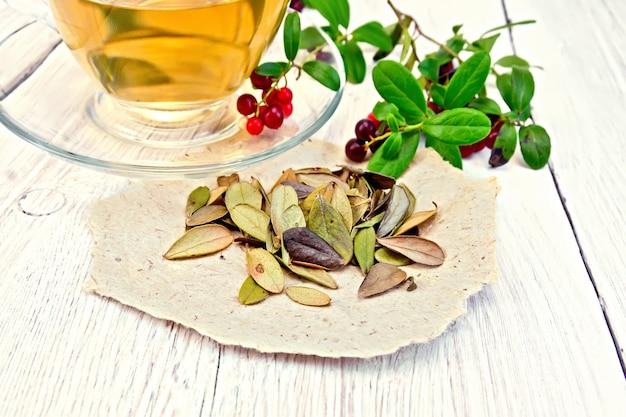 紙の上の乾燥したリンゴンベリーの葉、ガラスのコップのお茶、赤いビルベリーの明るい木の板の背景にベリーと緑の葉