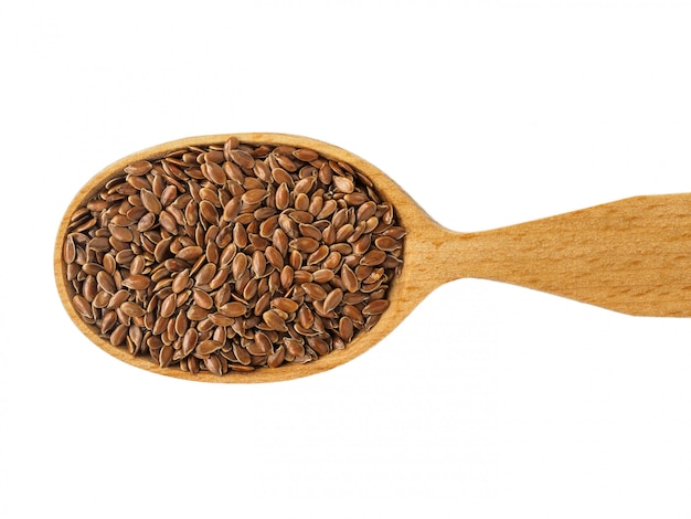 Dry linum seeds in a wooden spoon on a white background.