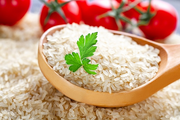 Dry long rice in wooden spoon with ripe tomatoes cherry and fresh green parsley.