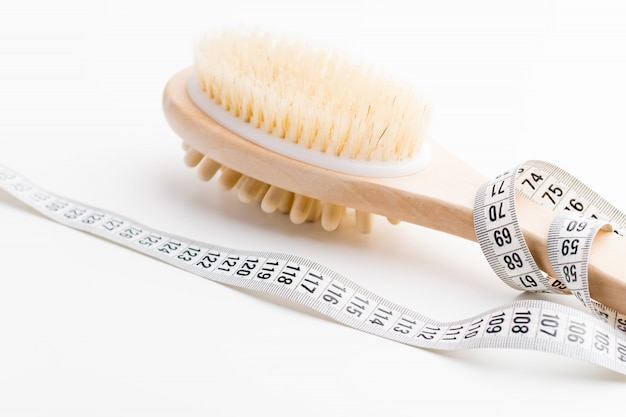 Dry massage brush with tape measure on white desk. health and diet.