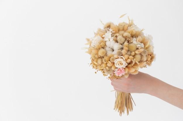 Сухой смешанный букет из разных цветов в женской руке на белой поверхности, дающей подарок на праздничную праздничную открытку