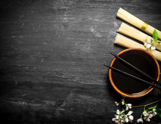 Сухая лапша с соевым соусом и вишневыми ветками на черном деревянном фоне