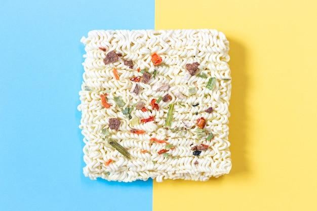 青と黄色の背景にスパイスと麺を上から見る
