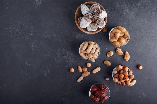 Сухие орехи и фрукты в стеклянной чашке на сером фоне, вид сверху.