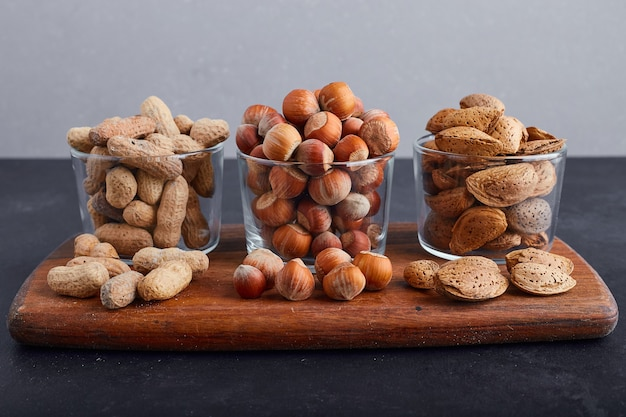 Dry nuts in glass cups on a wooden platter on blue background.