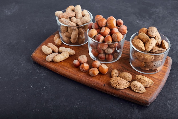 Dry nuts in glass cups on a wooden platter, top view.