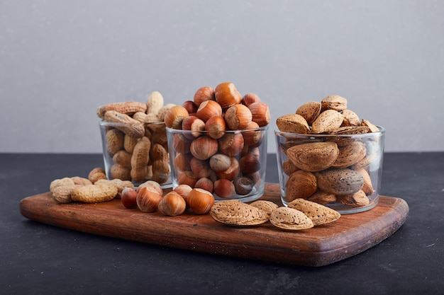 Dry nuts in glass cups on a wooden platter.