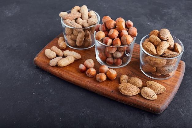 Сухие орехи в стеклянных чашках на деревянном блюде, вид сверху.
