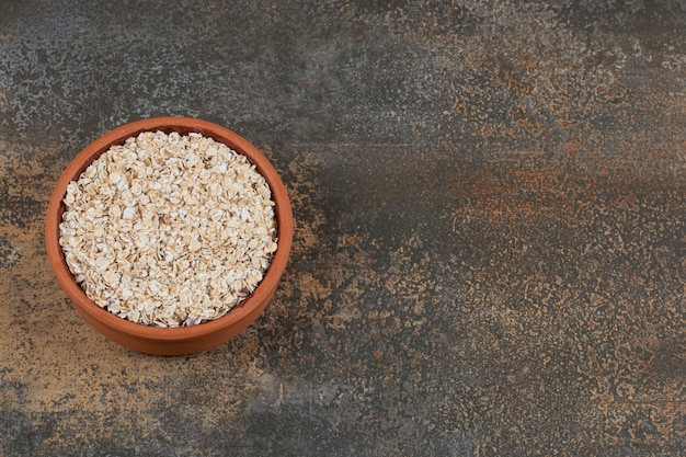 Dry oat flakes in ceramic bowl.