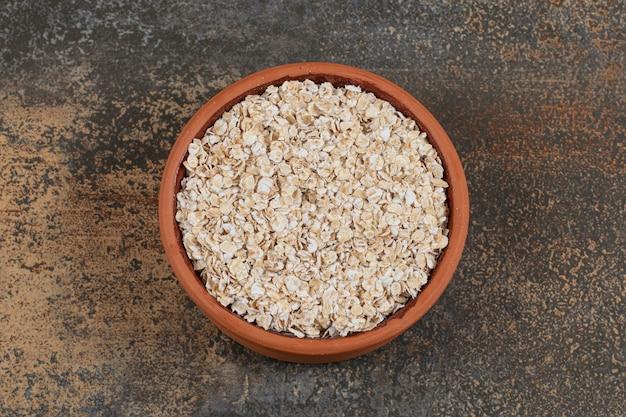 Fiocchi d'avena secchi in una ciotola di ceramica.