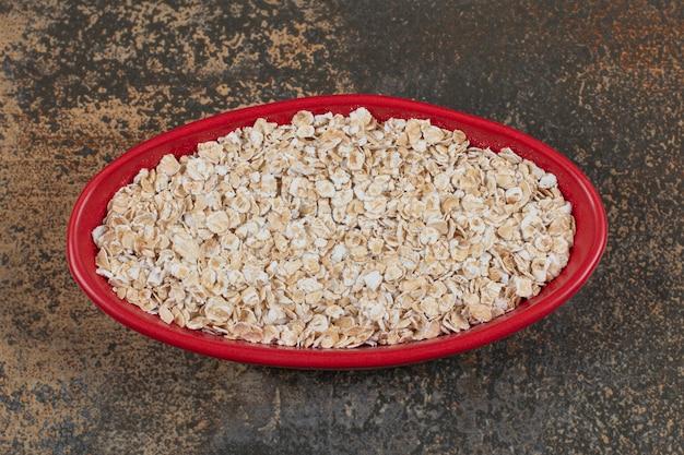 赤いボウルでオーツ麦フレークを乾燥させます。