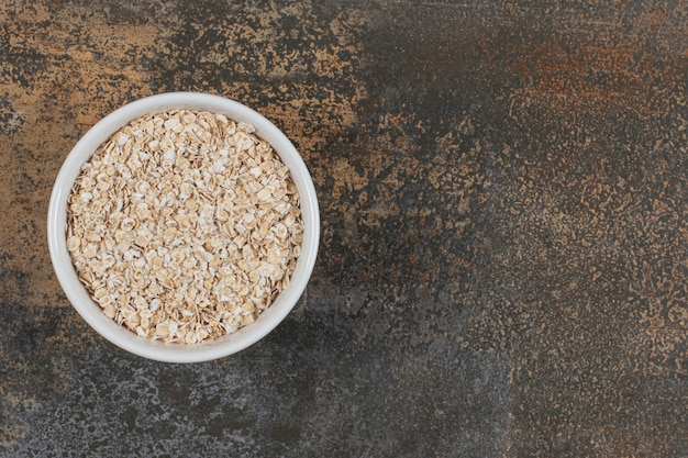 白いボウルにオーツ麦フレークを乾かします。