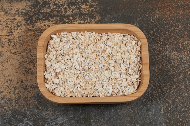 Dry oat flakes on wooden plate.