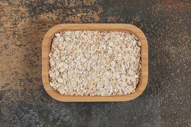 Fiocchi d'avena secchi sul piatto di legno.