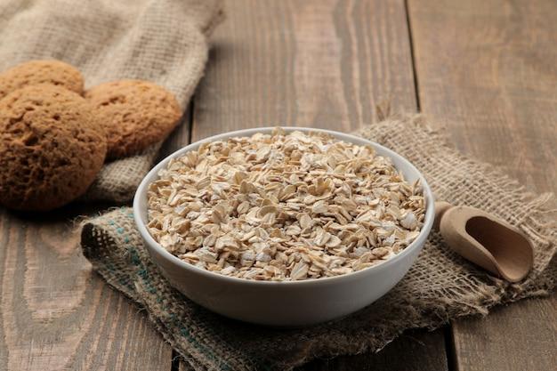 白いボウルと木のスプーンでオートミールとオートミールのクッキーを乾かします。食物。健康食品。茶色の木製テーブルの上。
