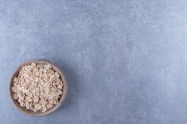 Farina d'avena secca in una ciotola, sullo sfondo di marmo.