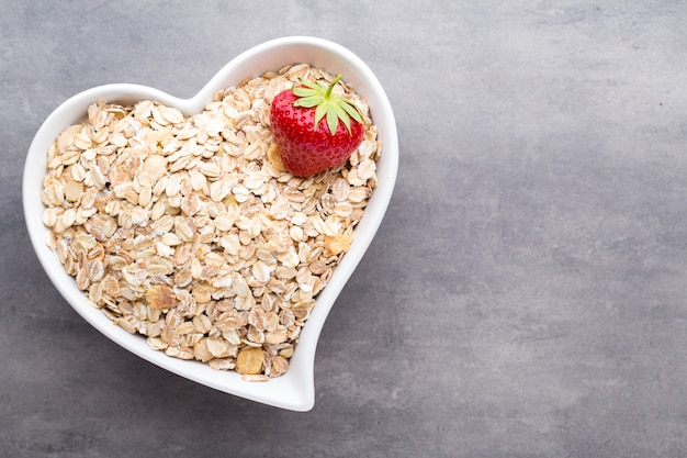 Dry oatmeal with strawberry in a bowl