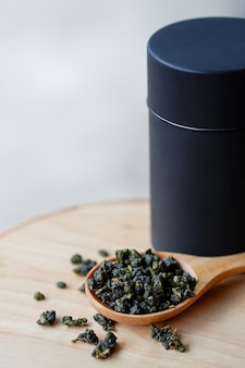 木のスプーンとテーブルの上の紅茶の葉の瓶に濃い緑色の乾いたウーロン茶または中国茶