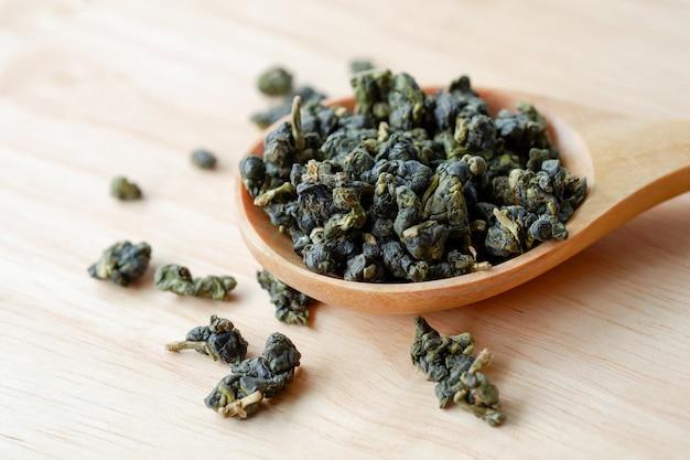 健康食品のテーブルの概念上の木のスプーンで濃い緑色のドライウーロン茶または中国茶