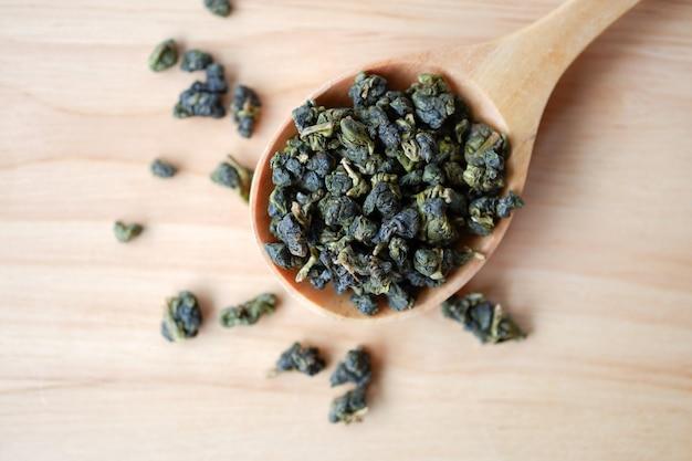 木の床に木のスプーンで濃い緑色の乾いたウーロン茶または中国茶