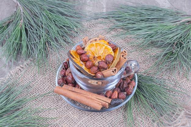 Asciugare le fette d'arancia con i fianchi e la cannella in una tazza di vetro.