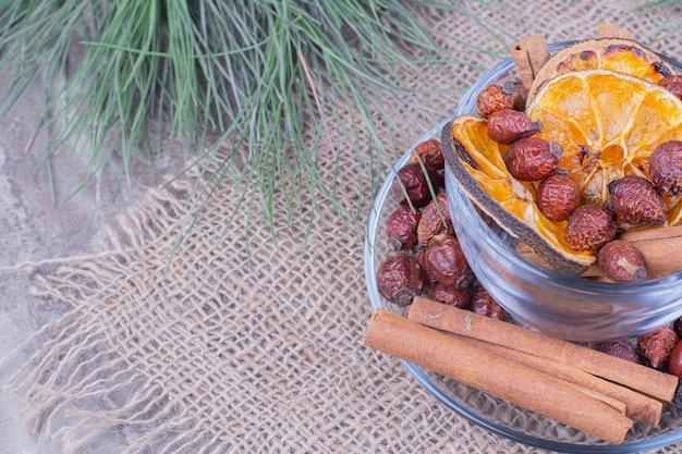 Fette di arance secche e fianchi con bastoncini di cannella in una tazza di vetro