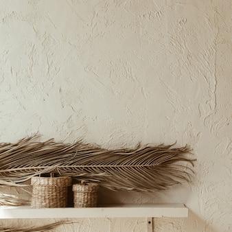 Сухая ветвь пальмового листа и шкатулки из ротанга на бетонной стене. дизайн интерьера.