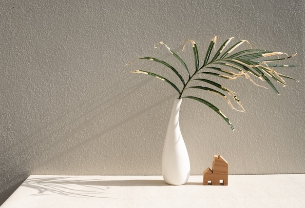 Dry palm leaves in beautiful white ceramic vase and house model on earth tone  table cement  wall surface  and copy space