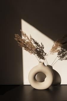 세련된 꽃병에 마른 팜파스 풀 리드. 벽에 그림자. 태양 빛에 실루엣입니다.