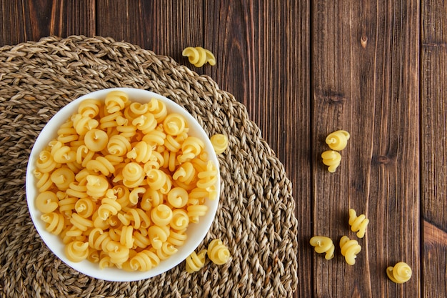 Dry pasta in a bowl on wooden and wicker placemat background. flat lay.