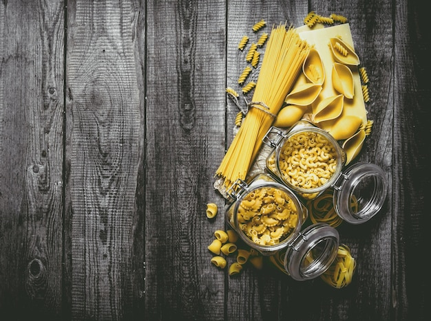 Dry pasta in cans and mixed pasta with spaghetti on wooden table. top view
