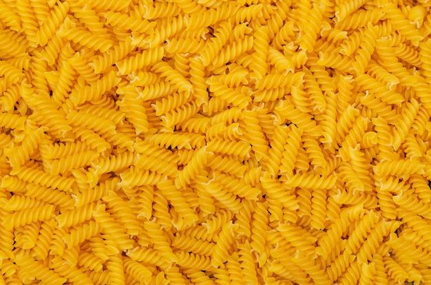Сухая паста фузилли фон. итальянская еда. скопируйте пространство.