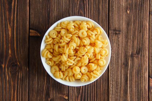Сухие макароны в миску на деревянном столе. плоская планировка