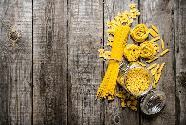 缶でパスタを乾かし、パスタとスパゲッティを混ぜます。木製の背景に。テキスト用の空き容量。上面図