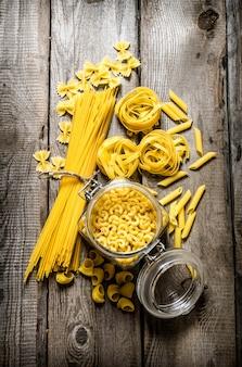 缶でパスタを乾かし、パスタとスパゲッティを混ぜます。木製の背景に。上面図