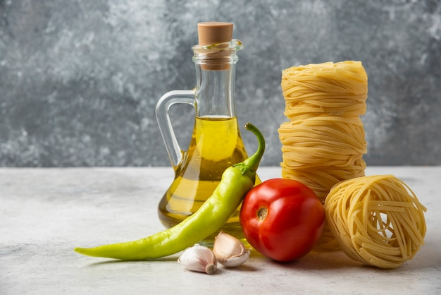 Dry pasta nests, bottle of olive oil and vegetables on white table.