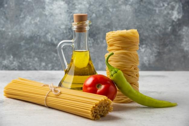 白いテーブルの上に乾いたパスタの巣、スパゲッティ、オリーブオイルと野菜のボトル。