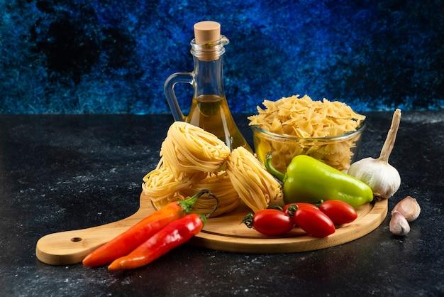 Pasta secca, olio e verdure su tavola di legno.