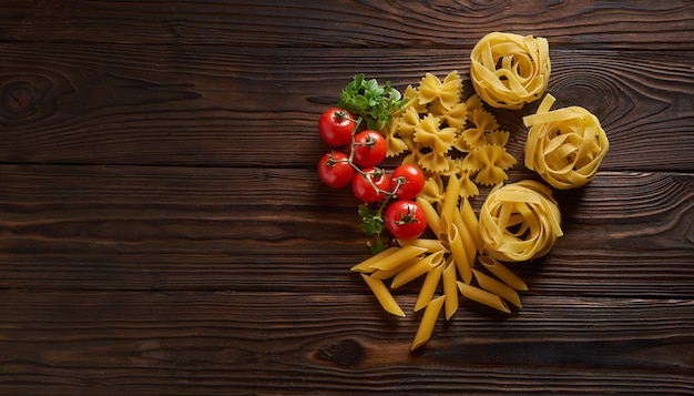 Сухие макароны пенне, фарфалле, тальятелле с базиликом и помидорами черри на деревянный стол. вид сверху с копией пространства