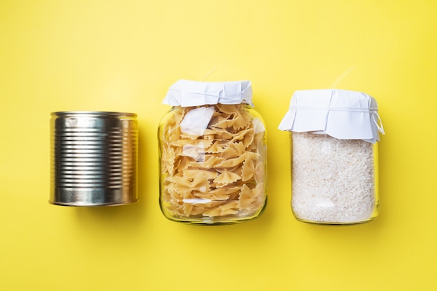 Dry pasta and rice in a glass jar and tin cans with canned food. concept of food storage, donations.