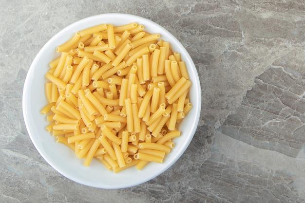 Сухие макароны в виде узких трубок в белой миске.