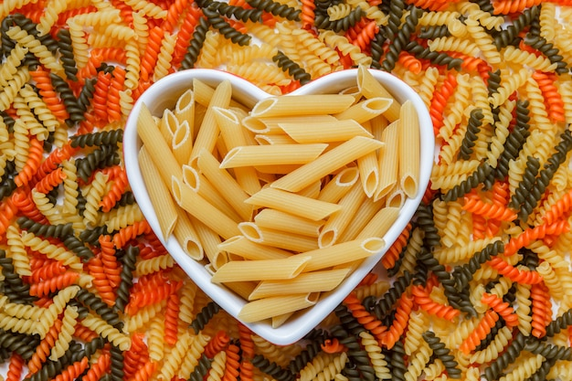 Dry penne pasta in a heart shaped plate flat lay on a colored fusilli table