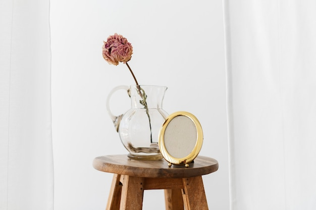Dry peony flower in a glass jug on a wooden stool in a white room
