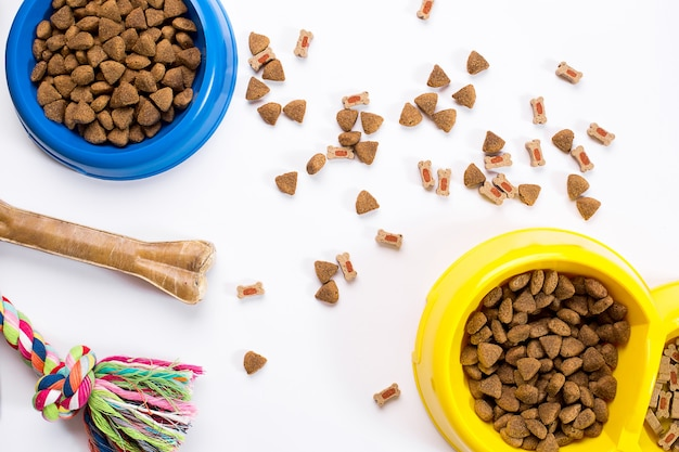 Dry pet food in bowl and toys for dogs on white background top view
