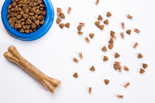 Dry pet food in bowl on white background top view